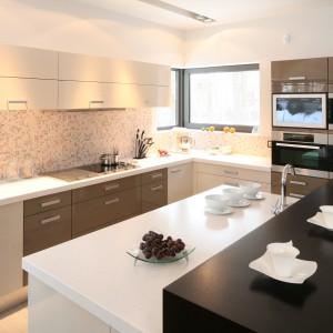 Dzięki temu, że ścianę nad blatem kuchennym wykończono delikatną mozaiką, można było zastosować meble kuchenne w różnych barwach. Powierzchnie roboczą i zabudowę piekarnika oznaczono ciemniejszym kolorem. Projekt: Małgorzata Szajbel-Żukowska. Fot. Bartosz Jarosz.