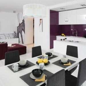 Pokryta fioletowym szkłem ściana nad blatem komponuje się kolorystycznie i nawiązuje do kompletu wypoczynkowego w salonie. Oba pomieszczenia tworzą jedną otwartą przestrzeń, a dzięki zastosowanym kolorom, spójną wizualnie całość. Projekt: Anna Maria Sokołowska. Fot. Bartosz Jarosz.