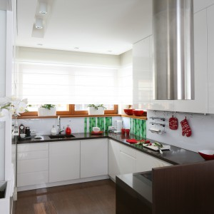 W niemal całkowicie białej kuchni, kolorowa tapeta ożywia wnętrze i nadaje mu charakteru. Bambus i biały storczyk w rogu nadają wnętrzu azjatyckiego klimatu. Projekt: Katarzyna Mikulska-Sękalska. Fot. Bartosz Jarosz.