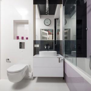 Fronty wysokich szafek w łazience pokryto czarno-białą tapetą. Na tle uniwersalnych bieli i czerni wybijają się akcenty w delikatnych liliowych odcieniach - kobiecy akcent w nowoczesnej zimnej przestrzeni. Fot. Decoroom.