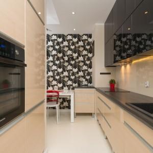 Meble kuchenne wykończono na połysk. Połyskująca jest również powierzchnia ściany nad blatem kuchennym. Odbijające otoczenie powierzchnie optycznie powiększają wąskie wnętrze kuchni. Fot. Decoroom.