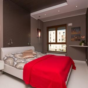 Ścianę za zagłówkiem łóżka pokryto tapetą z subtelnym, eleganckim wzorem. Oświetlenie zainstalowane w podwieszanym suficie urokliwie otacza przestrzeń wokół łóżka. Fot. Decoroom.