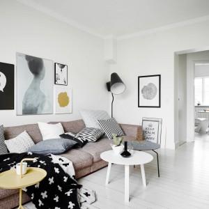Ciemne dodatki kontrastują z bielą ścian i podłóg. Wnętrze ocieplają tkaniny oraz poduszki dekoracyjne. Fot. Stadshem.