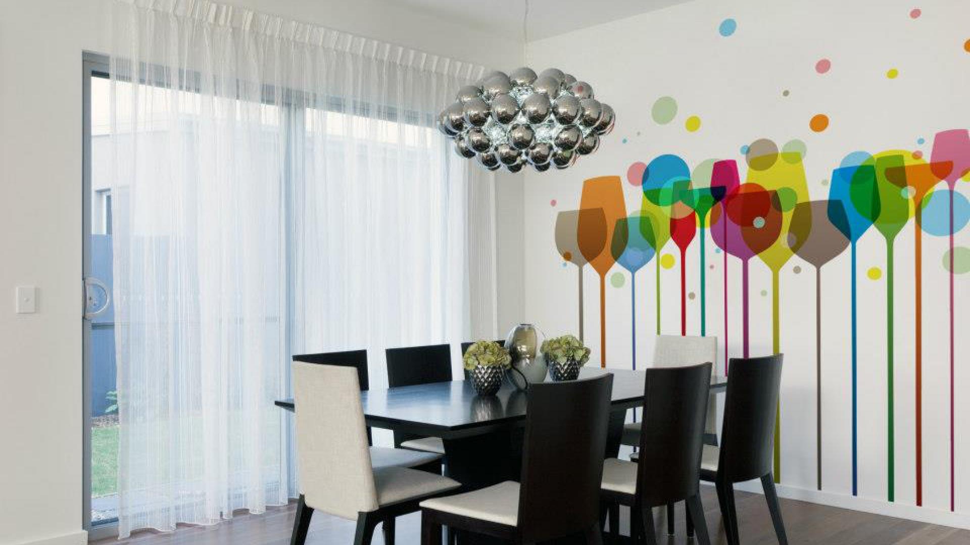 Ścianę w jadalni pokrywa fototapeta z grafiką, przedstawiającą różnokolorowe kieliszki. Paleta tęczowych barw ożywia powściągliwą aranżację wnętrza, utrzymanego w stonowanych kolorach. Fot. Minka.pl.