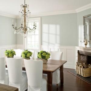 Przytulna jadalnia w klasycznym stylu. Elementy dekoracyjne w postaci francuskiego żyrandola nad stołem, zdobień wokół kominka i sztukaterii pod sufitem tonuje chłodny turkus na ścianach. Całość tworzy elegancką, świeżą kompozycję. Fot. Benjamin Moore.