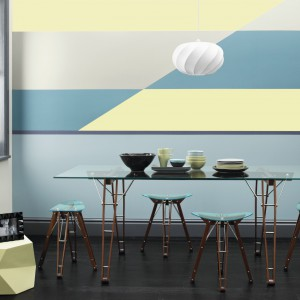 Kto powiedział, że pomalowana ściana musi być jednolita? Tutaj pokryto ją kilkoma kolorami farb, tworzącymi geometryczny dynamiczny wzór. Wprowadza on element nowoczesnego wzornictwa do wnętrza, który komponuje się z minimalistycznymi meblami. Fot. Crown Paints.