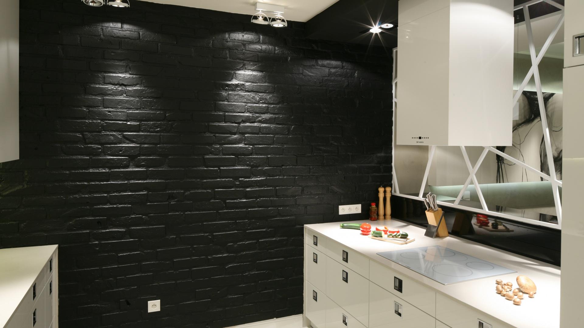 Kuchnię od salonu oddziela niezwykle efektowne przepierzenie, zlokalizowane nad blatem z płytka kuchenną. Projekt: Dominik Respondek. Fot. Bartosz Jarosz.