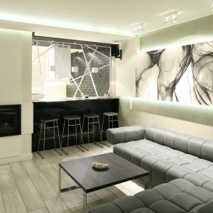 Biały ażurowy parawan pięknie komponuje się z dynamiczną grafiką na ścianie, stanowiąc dekoracyjny akcent zarówno kuchni, jak i salonu. Przy podzielonym przez przepierzenie blacie, ustawiono stołki, tworzące z niego bar. Projekt: Dominik Respondek. Fot. Bartosz Jarosz.