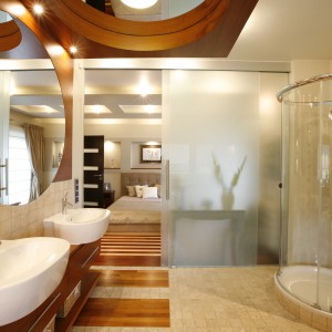 Do imponującego metrażem salonu kąpielowego można wejść bezpośrednio  z sypialni. Rozsuwane szklane drzwi z mlecznego szkła zapewniają dyskrecję osobom korzystającym z obu pomieszczeń jednocześnie. Projekt: Magdalena i Radosław Świgulscy. Fot. Marcin Onufryjuk.