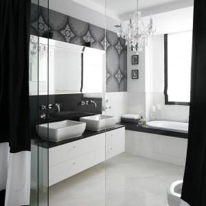 Elegancka łazienka urządzona jest w czerni i bieli, aby podkreślić spójność stylistyczna obu pomieszczeń na  ścianie łazienki i sypialni zastosowano identyczna tapetę. Projekt: Magdalena Smyk. Fot. Bartosz Jarosz.