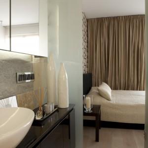 Drzwi z mlecznego szkła oddzielają łazienkę od znajdującej się obok sypialni. Oba pomieszczenia utrzymane są w ciepłej kolorystyce; w aranżacji zastosowano ciemne drewno i naturalny łupek. Projekt: Magdalena Smyk. Fot. Bartosz Jarosz.