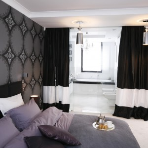 Sypialnia i łazienka zajmują jedno duże pomieszczenie. Oddzielone zostały szklanymi rozsuwanym drzwiami, a od strony sypialni także kotarą. Projekt: Magdalena Smyk. Fot. Bartosz Jarosz.