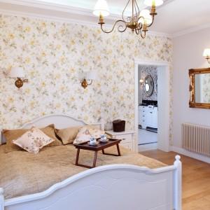 Ten dom urządzony jest w stylu angielskim. Właściciele mają do dyspozycji łazienkę znajdująca się tuż przy sypialni. W obu pomieszczeniach zastosowano kwiatowe tapety na ścianach i stylowe wyposażenie. Projekt:  Maciej Bołtruczyk, Emilia Gałecka-Kościańska. Fot. Monika Filipiuk-Obałek.