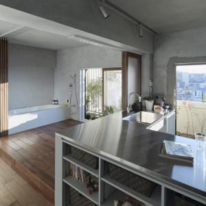 We wnętrzu panuje nowoczesna funkcjonalność. Proste, oszczędne formy, brak zbędnych dekoracji i cementowe ściany podkreślają stylistykę mieszkania. Kuchnia również została utrzymana w nowoczesnym stylu, którego przykładami są podwieszany zlewozmywak i gładki, stalowy blat. Fot. Koichi Torimura.