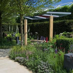 """Granitowe bloki stanowią statyczny element pośród dynamicznej kompozycji kolorowych roślin. Ogród """"Hope on the Horizont"""". Proj. Matt Keightley. Fot. RHS Chelsea Flower Show."""