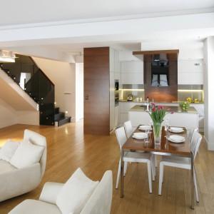 W otwartej strefie dziennej przestrzeń salonu płynnie łączy się z jadalnią, a następnie kuchnią. Elementem spajającym całość jest stonowany kolor ścian oraz ciepło drewnianej podłogi. Projekt: Kamila Paszkiewicz. Fot. Bartosz Jarosz.