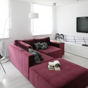 W skąpany w bieli salonie duża wygodna kanapa narożna wyznacza strefę wypoczynkową. Jej piękny, bakłażanowy kolor doskonale koresponduje z fioletem ściany w kuchni. Projekt: Anna Maria Sokołowska. Fot. Bartosz Jarosz.