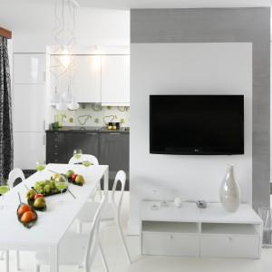 Dużym przestronnym wnętrzu kuchnia salon i jadalnia tworzą jedną spójną stylistycznie całość. Dominuje tu biel, która podkreśla świeżość aranżacji. Projekt: Jolanta Kwilman. Fot. Bartosz Jarosz.