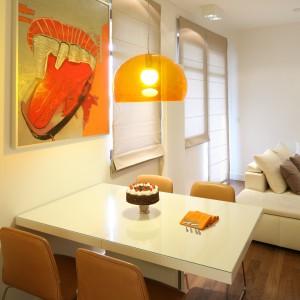 Krzesła w jasnym, brązowym kolorze doskonale pasują do pomarańczowej lampy oraz do wyrazistego obrazu. Fot. Bartosz Jarosz.