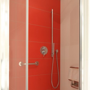 Jedynym mocnym akcentem w łazience jest czerwona ścian pod prysznicem. Fot. Bartosz Jarosz.