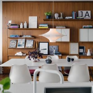 Stół jadalniany spaja stylistycznie kilka pomieszczeń. Biały blat koresponduje ze stylistyką kuchni, podczas gdy akcesoria nawiązują kolorami do dekoracji na półkach w jadalni. Z kolei siedziska krzeseł pasują do przytulnych tekstyliów w salonie. Fot. Alvhem Makleri.