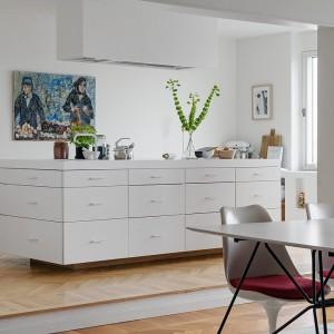 W kuchni dominującym elementem jest obszerna, biała wyspa kuchenna. Nowoczesny mebel pełen jest pomniejszych szuflad, oferujący sporo miejsca do przechowywania sprzętów kuchennych. Fot. Alvhem Makleri.