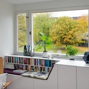 Pod oknem w salonie zlokalizowano niewielki kącik czytelniczy. W zabudowie, będącej przedłużeniem parapetu zaplanowano praktyczne podręczne półki oraz wygodne siedzisko. Całości dopełnia nowoczesny, designerski fotel. Fot. Alvhem Makleri.