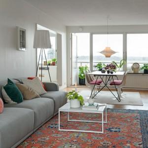 Przytulny klimat w pomieszczeniu tworzy wzorzysty barwny dywan, pasujące do niego kolorystycznie tekstylia oraz drewniana zabudowa ściany w jadalni. Domową atmosferę stwarzają również drewniana podłoga i obrazki na ścianie nad kompletem wypoczynkowym. Fot. Alvhem Makleri.