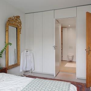 W sąsiedztwie sypialni zlokalizowano łazienkę. Prowadzą do niej drzwi schowane wśród białej zabudowy. Fot. Alvhem Makleri.