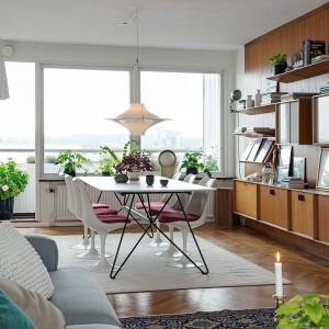 Ścianę w jadalni pokrywa drewniana zabudowa, w postaci płyty, do której przytwierdzono półki i szafki. Ciepły odcień drewna komponuje się z kolorem parkietu na podłodze. Stylistycznie przywodzą one na myśl mieszkania z lat 70. Fot. Alvhem Makleri.