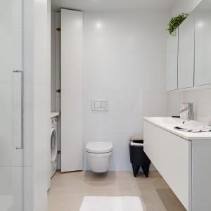 W łazience króluje kolor biały. Wraz z gładkimi frontami mebli bez uchwytów tworzy czystą, oszczędną i nowoczesną przestrzeń. Za wysokimi drzwiami schowano sprzęt AGD. Fot. Alvhem Makleri.