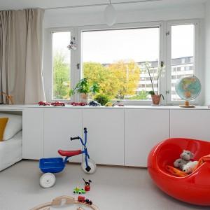 W pokoju dziecięcy również są duże okno. Wzdłuż nich wykonano białą zabudowę. Jest ona praktyczna oraz nie zabiera dużo przestrzeni. Biały kolor dodatkowo optycznie powiększa wnętrze. Ciekawym fantazyjnym akcentem jest czerwone siedzisko. Fot. Alvhem Makleri.