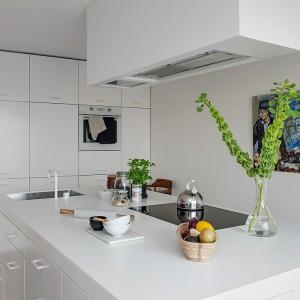 Na wyspie połączono kilka funkcji: blatu kuchennego, powierzchni do gotowania oraz zmywania. Duży praktyczny mebel uzupełnia wysoka zabudowa kuchenna. Fot. Alvhem Makleri.