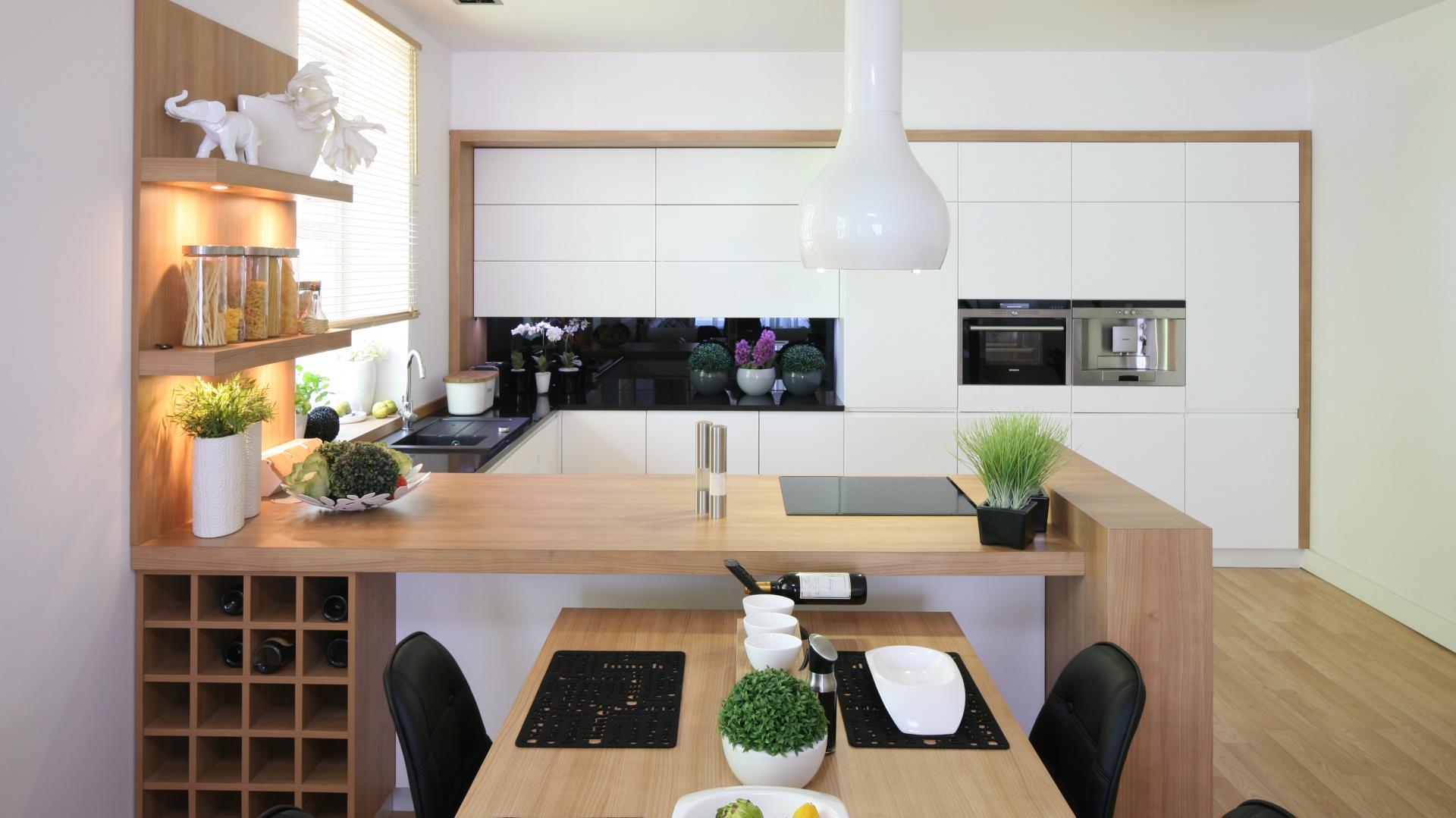Biały kolor optycznie powiększa wnętrze. Wokół obudowy zastosowano estetyczne obramowanie w kolorze dominującego w przestrzeni drewna. Projekt: Małgorzata Błaszczak. Fot. Bartosz Jarosz.