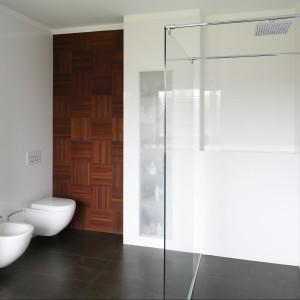 Chłodna, minimalistyczna aranżacja salonu kąpielowego została ocieplona za pomocą parkietu  z drewna egzotycznego mebrabu, ale zastosowanego nietypowo, bo na ścianie. Projekt: Piotr Stanisz. Fot. Bartosz Jarosz.