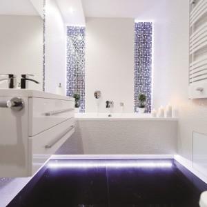Łazienka jest elegancka i relaksująca zarazem. Oświetlenie eksponuje wyjątkową, połyskującą fakturę białych, połyskujących płytek ceramicznych, a czarnej mozaice nadaje błękitną poświatę. Projekt: Izabela Balbus. Fot. Marta i Michał Rudiak.