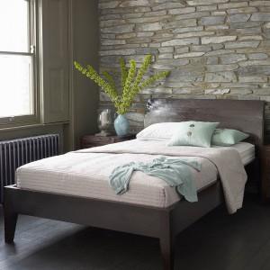 Kamień o nieregularnych obrysach tworzy ciekawą dekorację sypialni. Fot. Lombock.
