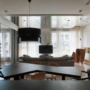 Jadalnię stanowi elegancki stół o oryginalnym, fantazyjnym kształcie, korespondujący ostrymi liniami z ciekawym zegarem ściennym w salonie. Fot. Kyle You.