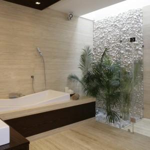 Ściana nad wanną i podłoga wykończone zostały trawertynem. W strefie prysznica z kolei królują białe otoczaki. Projekt: Katarzyna Mikulska-Sękalska. Fot. Bartosz Jarosz.