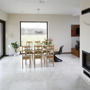 Dwa krzesła, które pozornie nie pasują do aranżacji stołu stanowią wizualną ramę, łączącą jadalnię z jej otoczeniem. Czarne siedzisko koresponduje z czarnymi krzesłami i blatem w kuchni, a z poziomu salonu pasuje również do obramowania kominka. Z kolei przezroczyste krzesło stylistycznie nawiązuje do panoramicznego przeszklenia, znajdującego się za nim. Projekt: Piotr Stanisz. Fot. Bartosz Jarosz.