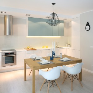 W kuchni dominują chłodne barwy: pastelowy turkus, jasne szarości i biel, zwieńczone metalowymi elementami. Drewniany stół o ciepłej barwie przełamuje chłód pomieszczenia i czyni je przytulniejszym. Krzesła z białymi siedzeniami i drewnianymi nogami pasują stylistycznie do całości aranżacji. Z kolei czarne elementy dekoracyjne łączące nogi krzeseł korespondują z nowoczesnym żyrandolem o geometrycznej formie. Projekt: Anna Maria Sokołowska. Fot. Bartosz Jarosz.