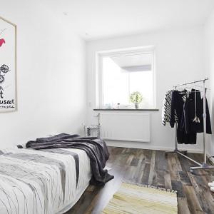 W jednej z sypialni nad pojedynczym łóżkiem zawieszono nowoczesną grafikę. Czerwień z plakatu delikatnie ożywia wnętrze, utrzymane w stonowanych barwach i bazujące na kontrastach czerni i bieli. Fot. Vastanhem.