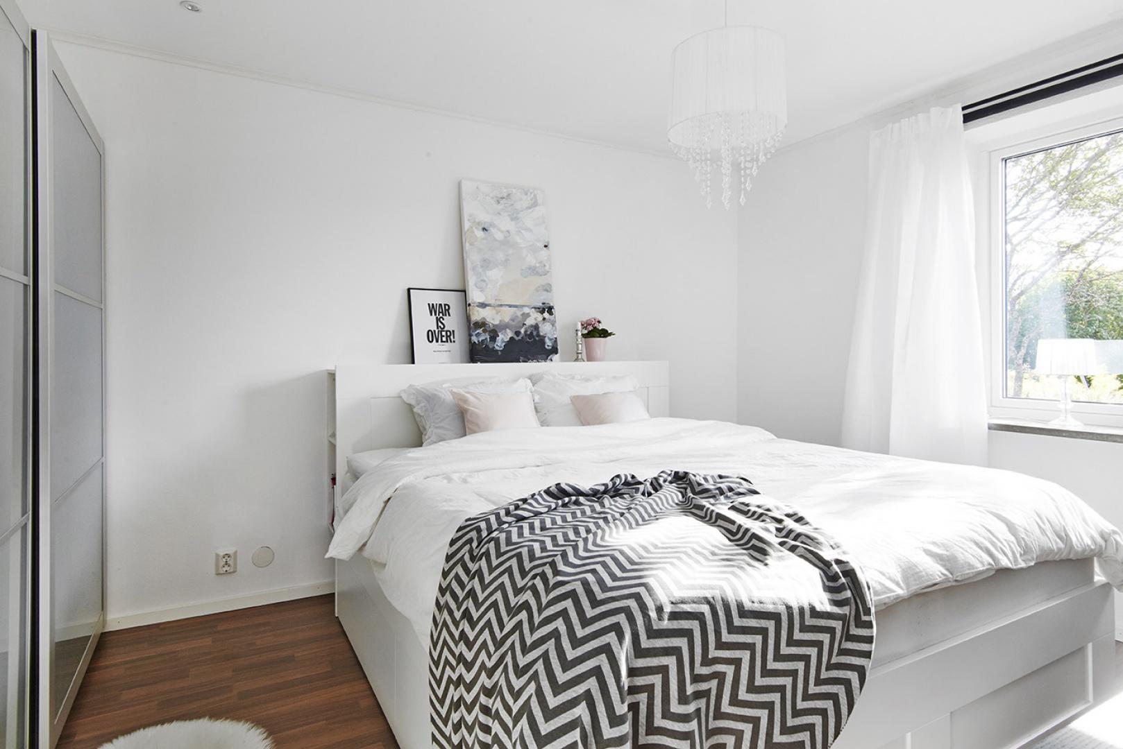 Przepiękna sypialnia utrzymana w jasnej kolorystyce. Dominującą biel urozmaicają delikatne pastelowe poduszki, wzorzysta czarno-biała narzuta z opartowskim motywem, a cieplejszym akcentem jest drewniana podłoga. Żyrandol wprowadza do wnętrza klimat glamour. Fot. Vastanhem.