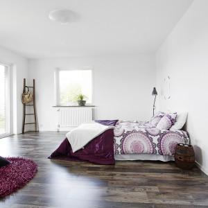 Bardzo duża, przestronna sypialnia. Białe ściany i oszczędne umeblowanie ocieplają drewniana podłoga i wzorzyste kolorowe tkaniny. Drabina w rogu pomieszczenia pełni funkcję dekoracyjną oraz może posłużyć za wieszak. Fot. Vastanhem.
