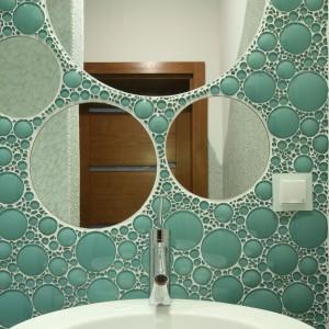 Okrągłe lustra różnej wielkości nawiązują do okrągłych elementów szklanej mozaiki na ścianie. Projekt: Karolina Łuczyńska. Fot. Bartosz Jarosz.
