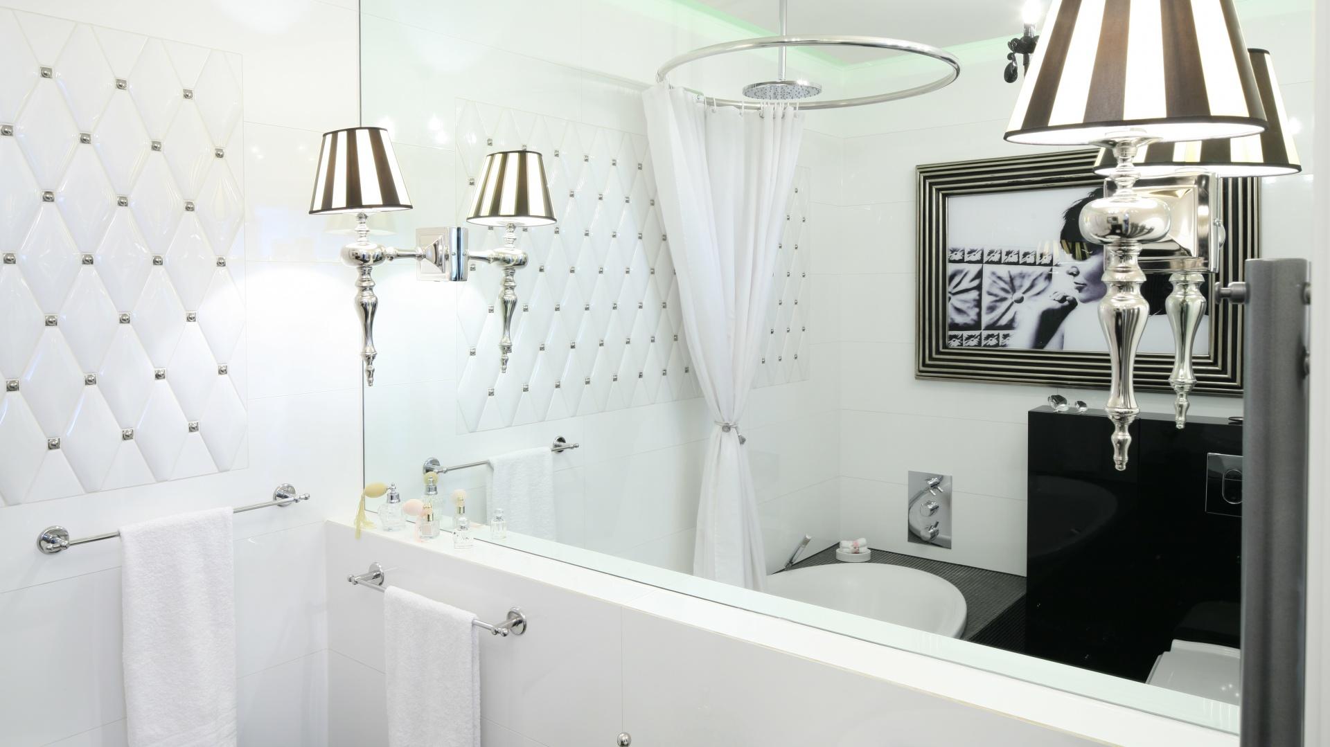 Tafla lustra została zamocowana na ścianie nad umywalką. Odbija się w niej zdjęcie w stylowej ramie umieszczone naprzeciw, do daje ciekawy efekt dekoracyjny. Projekt: Małgorzata Galewska. Fot. Bartosz Jarosz.