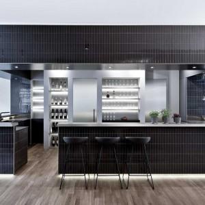 Kuchnię zlokalizowano w dużym, przestronnym kubiku. Jego powierzchnię od strony strefy dziennej wykończono efektownymi czarnymi kaflami. Fot. www.suite030.com.