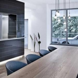 Sąsiadujący z kuchnią stół barwą komponuje się z drewnianą podłogą. Otaczają go eleganckie, czarne krzesła. One z kolei korespondują kolorem z wykończeniem kuchni. Strefa ta jest idealna jako miejsce spotkań i konferencji. Fot. ww.suite030.com.