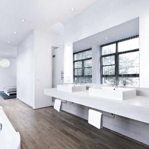 Esencja master bedroom. Sypialnia płynnie przechodzi w przestronną łazienkę w hotelowym stylu. Jednorodność powierzchni podłogi optycznie powiększa, i tak już duże, wnętrze. Kubistyczne umywalki z płytkimi misami, duże lustro bez ram i prosty, surowy blat podumywalkowy tworzą minimalistyczną elegancję. Fot. www.suite030.com.