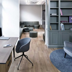 Gabinet utrzymano w kolorach delikatnych szarości. Miękki, przytulny fotel i szarozielone meble z frezowanymi frontami nadają wnętrzu klasycznego wyrazu, podczas gdy krzesło przy biurko i lampka są pochwałą nowoczesnej stylistyki. Fot. www.suite030.com.